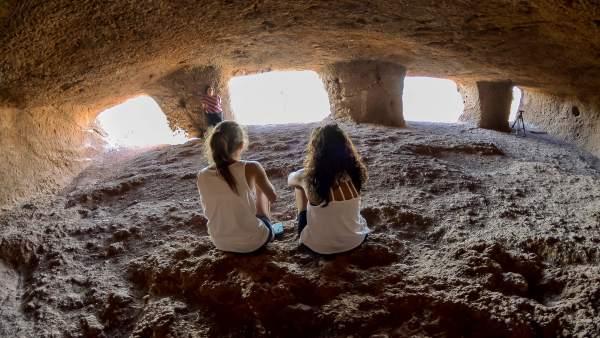 Dos chicas en una cueva del yacimiento de cuatro puertas
