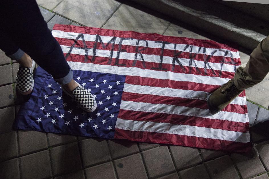 La 'Amerikkka' de Trump. Manifestantes pisan una bandera estadounidense con la palabra