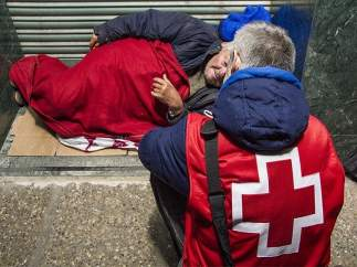 Un voluntario de CRuz Roja ayuda a una sintecho.