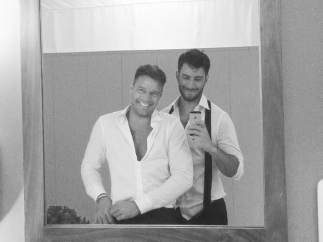 Ricky Martin sonríe junto a su novio frente a un espejo