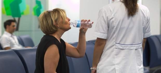 Una mujer bebe agua en Urgencias