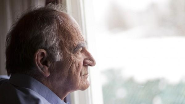 Una persona mayo mirando por la ventana.