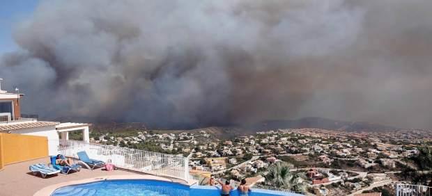 Unos vecinos observan el avance del incendio de Benitatxell