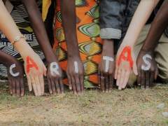 Varias personas forman con sus manos el nombre de Cáritas