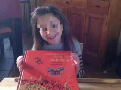La niña Nadia Nerea posa con el libro 'Alas de mariposa'.