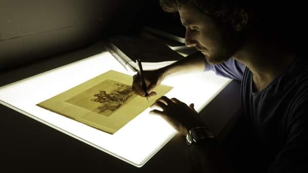 Uno de los alumnos de la escuela taller de la DPZ restaurando un grabado de Goya
