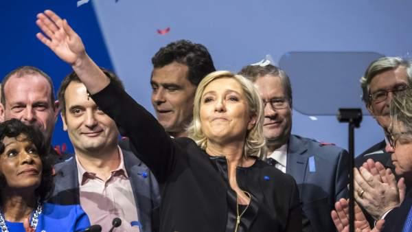 Marine Le Pen levanta la mano en el acto de apertura de campaña en Lyon.