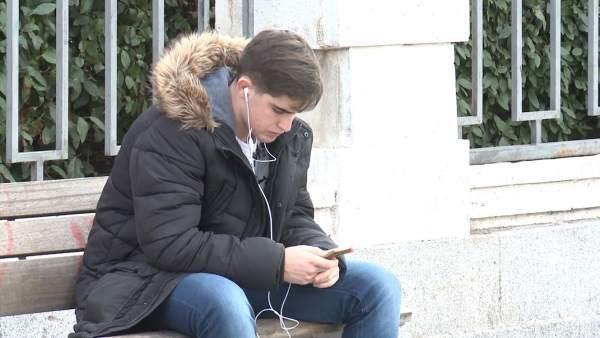 Un joven consulta su teléfono móvil