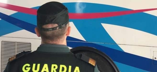 Agente de la Guardia Civil, ante un autobús escolar.