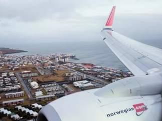 Un aparell de la companyia noruega sobrevola una ciutat portuària