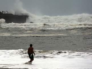 Un hombre se baña en San Sebastián, donde se ha decretado alerta por oleaje.