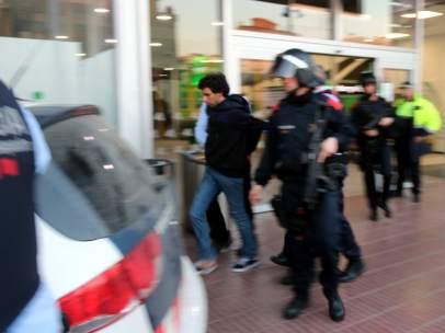 Los Mossos d'Esquadra llevándose al joven detenido en la estación del AVE de Girona.