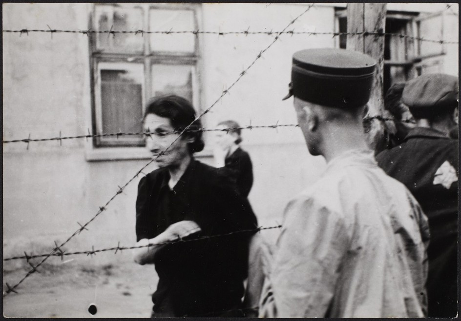 Henryk Ross - Ghetto police with woman behind barbed wire, 1942