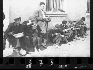 """Henryk Ross - """"Soup for lunch"""" (Group of men alongside building eating from pails), 1940-44"""