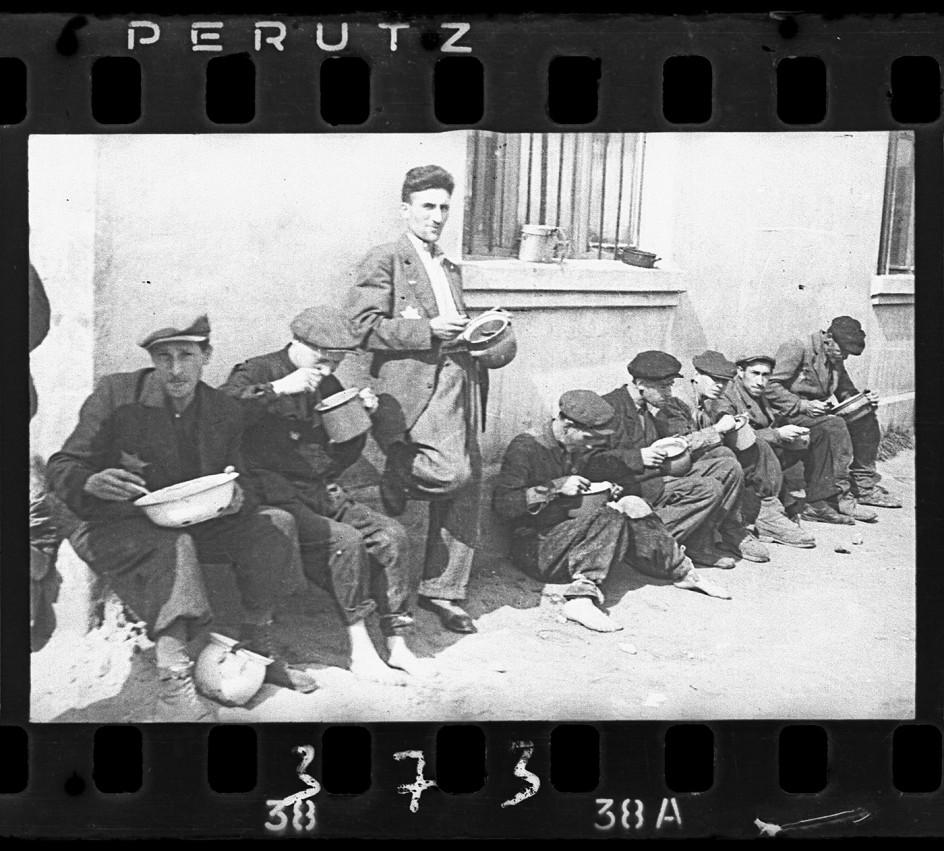 "Henryk Ross - ""Soup for lunch"" (Group of men alongside building eating from pails), 1940-44. Foto de Henryk Ross del momento de la comida en el gueto de Lódz"