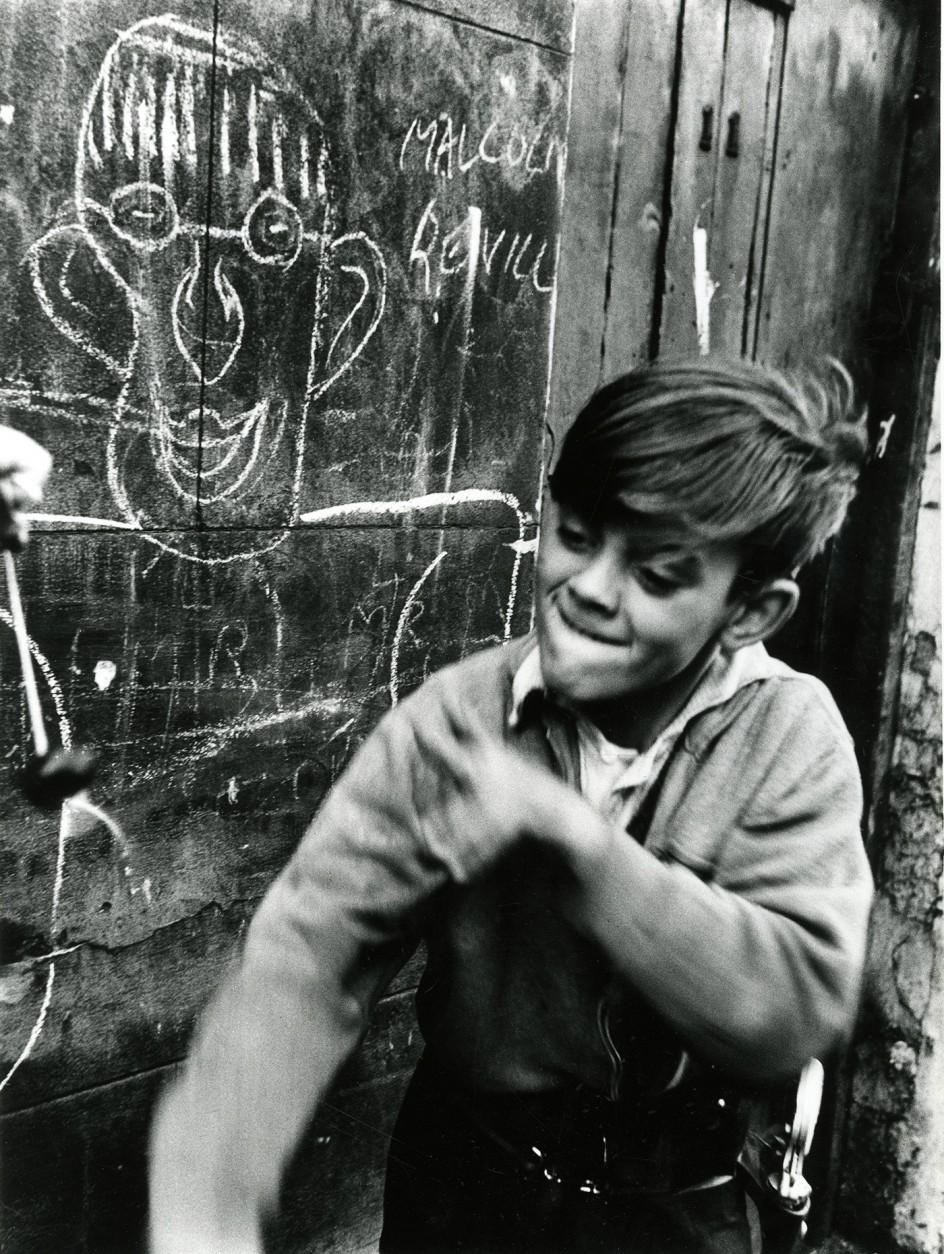 Roger Mayne - Boy playing conkers, Addison Place (N. Kensington), 1957 . Un niño jugando en la calle, en una foto de Roger Mayne de 1957