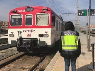 Una agent davant un tren de rodalies en l'estació d'Alacant Terminal