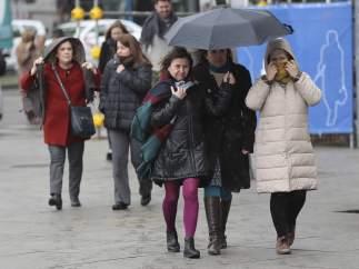 Varias personas se protegen del frío y la nieve en Madrid.