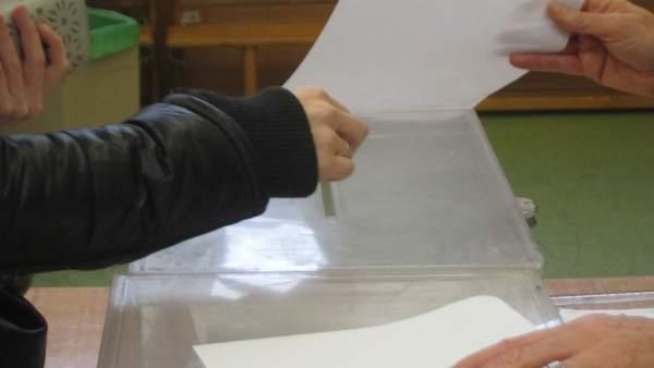 Una mano deposita una papeleta en la urna en un colegio electoral