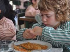 Niño comiendo en una escuela catalana, beca comedor.