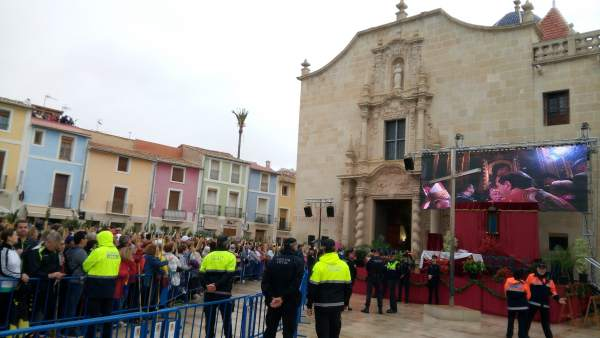 Los fieles siguen la misa en la plaza bajo la lluvia