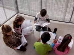 Alumnos leen sus libros de texto.