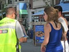 Agente cívico con dos turistas en Barcelona