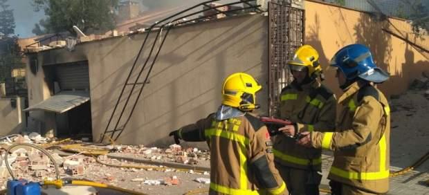 Efectivos de los Bombers junto a las ruinas de una casa de Collbató incendiada y derrumbada, probablemente por una explosión.