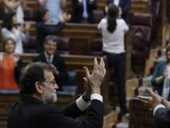 Rajoy aplaude con Iglesias de fondo.