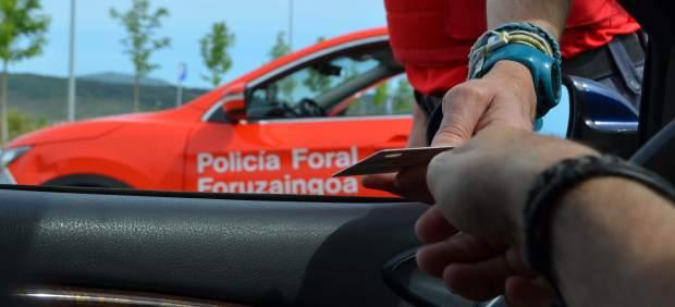 Un conductor entrega su documentación a un policía foral