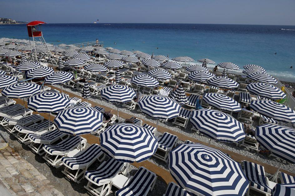 Ni un metro de playa libre. Sombrillas y tumbonas en un día de playa y sol en Niza (Francia).