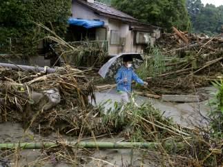 Una persona camina en una zona arrasada por las inundaciones en Japón.