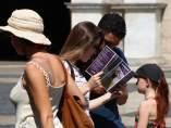 Un grupo de turistas mirando un folletín en la plaza Sant Jaume de Barcelona