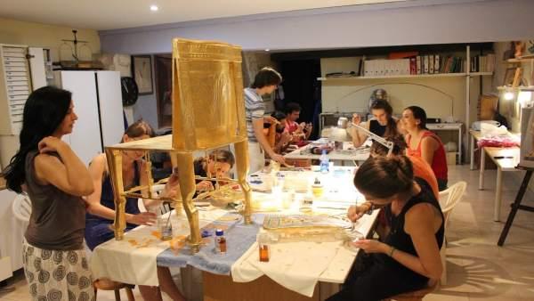 Toques de pan de oro finales al marco de madera del trono de Tutankamón