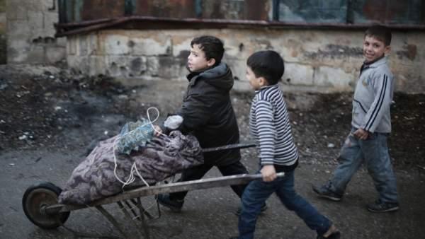 Niños empujan un carro en Ghuta Oriental, cerca de Damasco