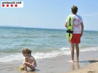 Un socorrista vigila el baño en una playa catalana