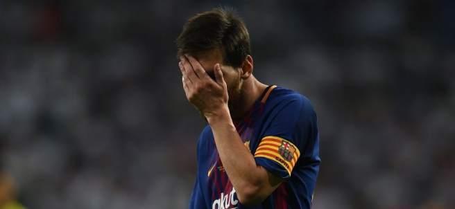Messi se tapa la cara durante el partido.