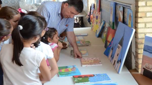 El alcalde de Palos de la Frontera, Carmelo Romero, visita un taller de pintura.