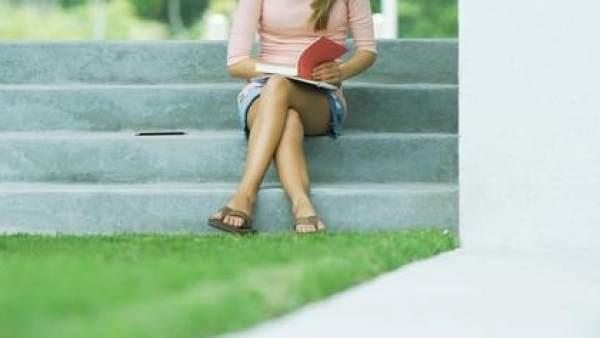 Una joven, sentada con las piernas cruzadas