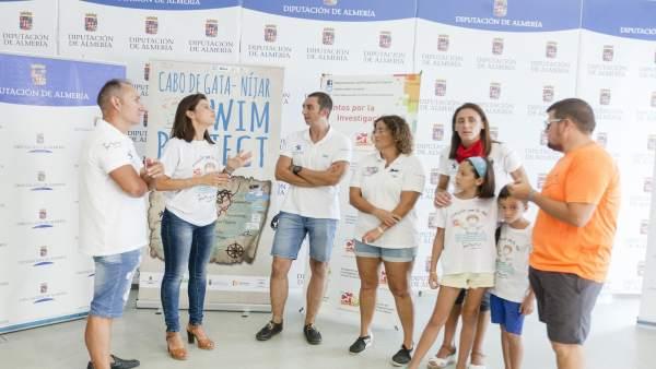 La diputada Ángeles Martínez junto a tres de los nadadores del reto solidario.