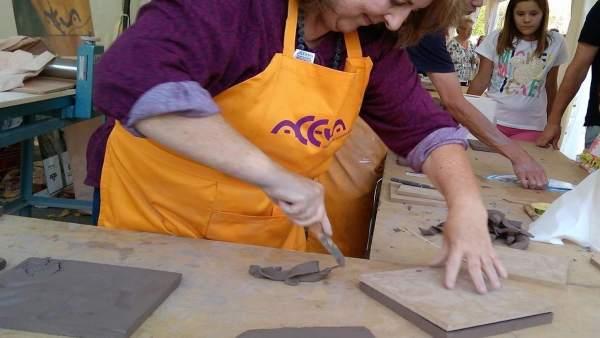 Una mujer recorta el barro utilizado para inmortalizar las huellas del mural