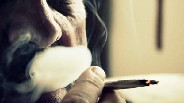 Un hombre fumando un porro.