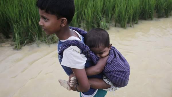 Un niño rohinyá portea a su hermana pequeña cruzando de Birmania a Bangladesh