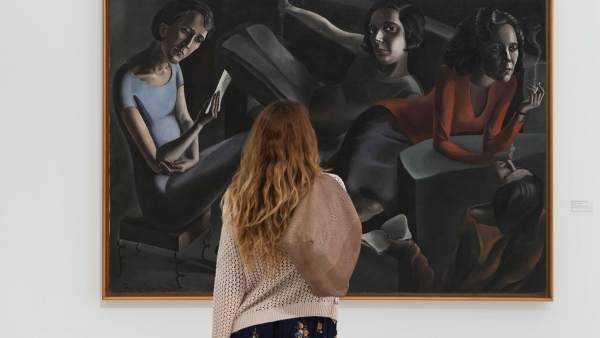 Una espectadora contempla 'La tertulia' de Ángeles Santos