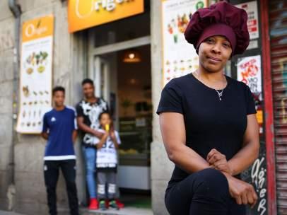 Kenia, con sus tres hijos en la puerta de la tienda donde trabaja