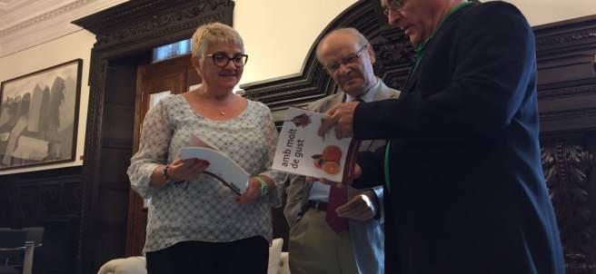 El alcalde Joan Ribó ojea la guía visual de la AVL 'Amb molt de gust'
