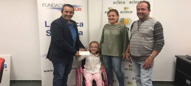Celia recibiendo el cheque para su tratamiento