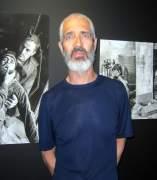El fotógrafo Alberto Prieto delante de imágenes suyas en la exposición
