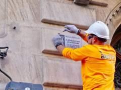 Un operario retira una placa franquista de una fachada de Barcelona.