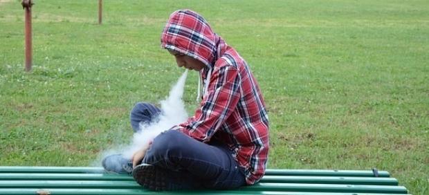Un joven, vapeando en un banco.